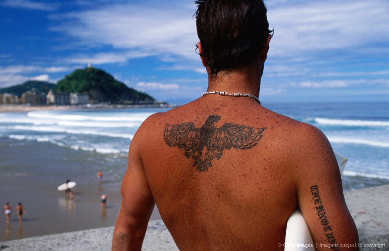 Tattooed surfer looking at beach, San Sebastian, Spain