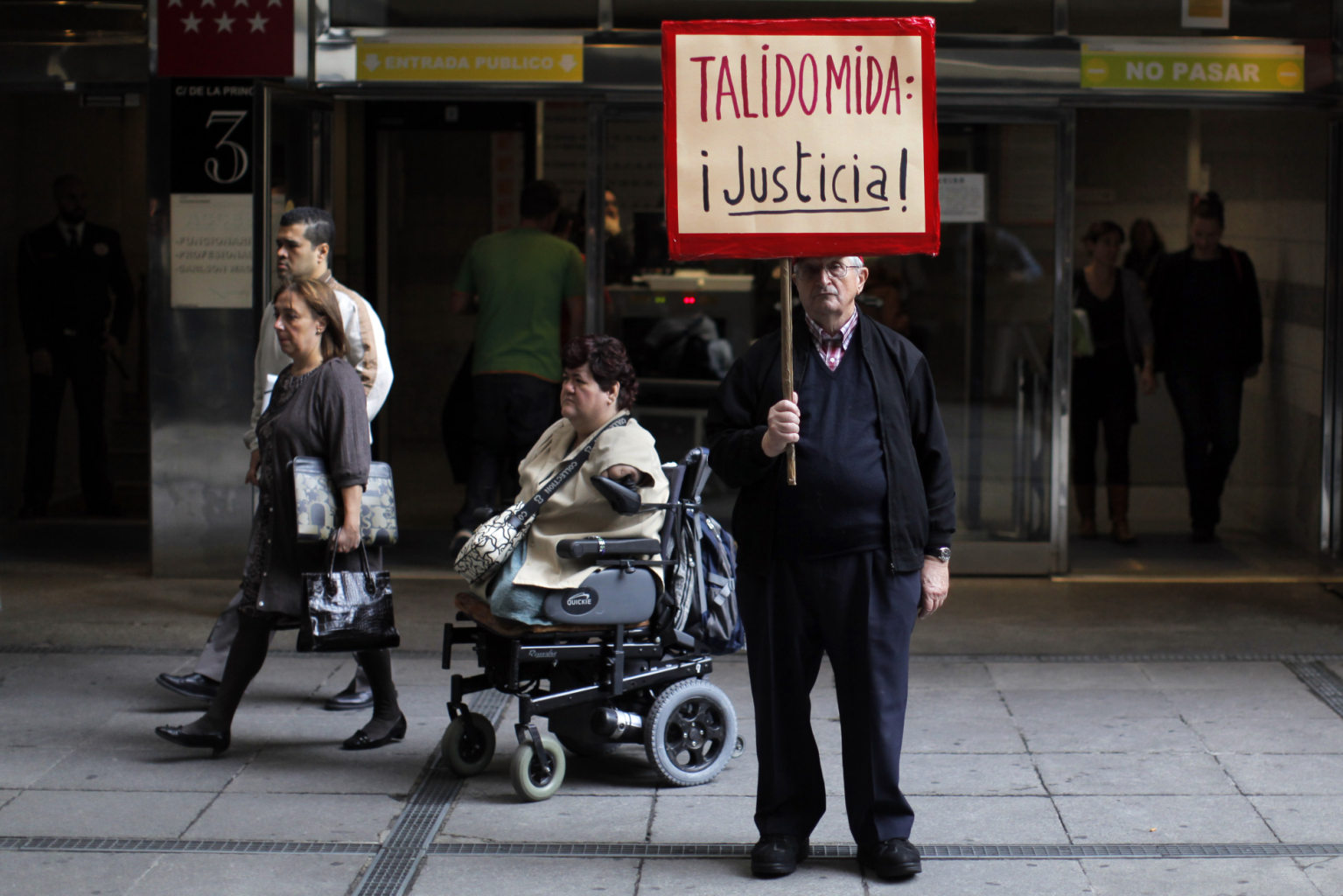 "A Thalidomide victim leaves court on a wheelchair, third left, as a protestor stands with a banner reading ""Thalidomide, Justice!"" outside Court during..."