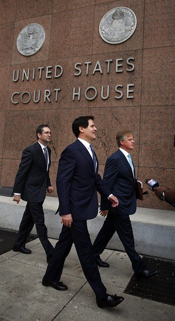 Dallas Mavericks owner Mark Cuban walks into the Earle Cabell Federal Courthouse for closing arguments with his lawyers, Tuesday, Oct. 15, 2013 in Dallas....