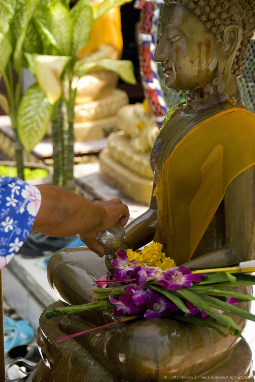 Person pouring water over Buddha statue at Temple of the Big Buddha, Fan Island, Koh Samui, Thailand