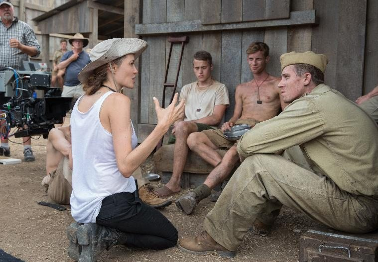 """In this image released by Universal Pictures, director Angelina Jolie, left, speaks with Garrett Hedlund on the set of """"Unbroken."""" (AP Photo/Universal..."""
